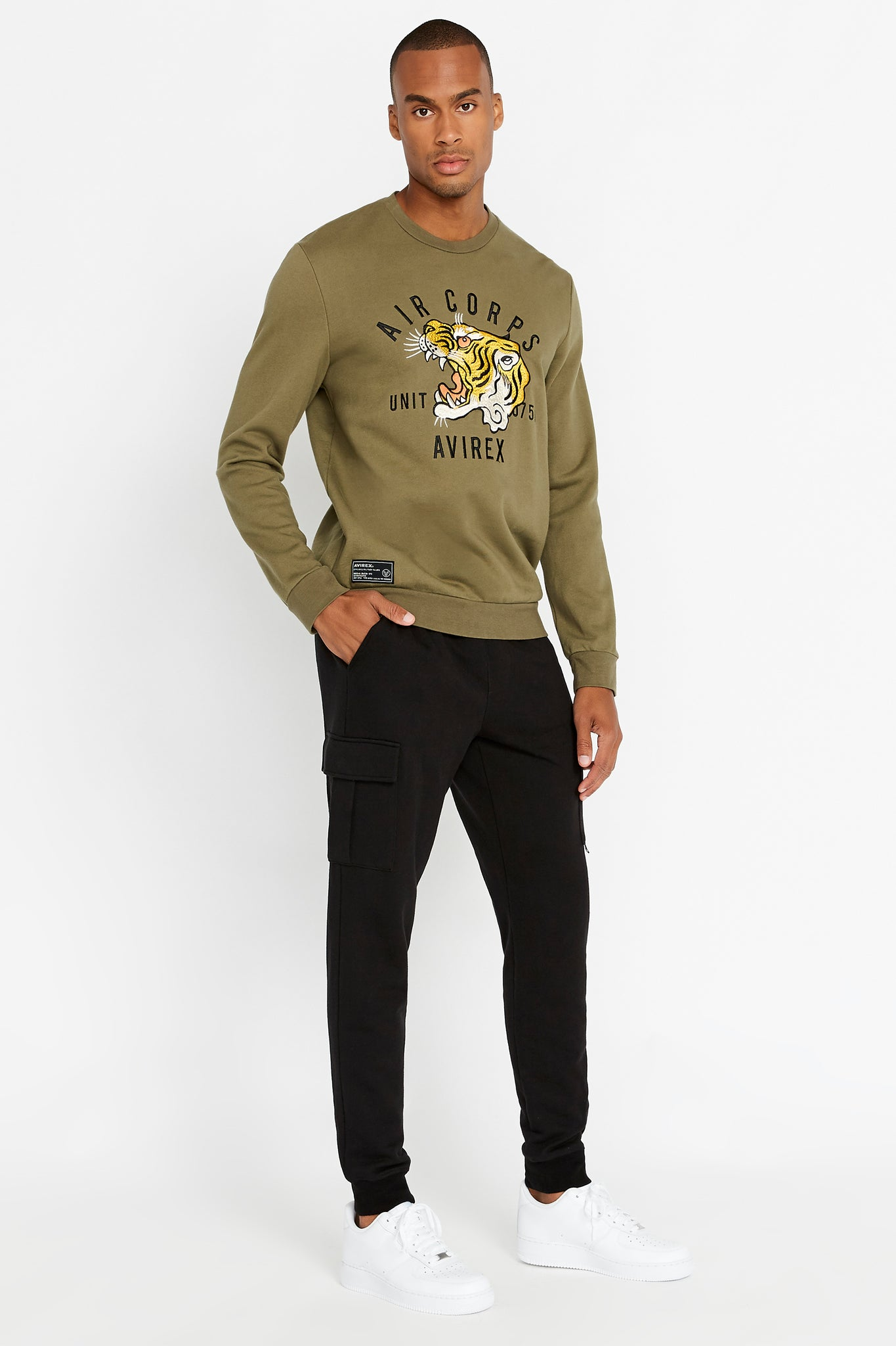 Side full view of men wearing an olive long sleeve crew neck sweater with front tiger embroidery and patch on right bottom and black pants