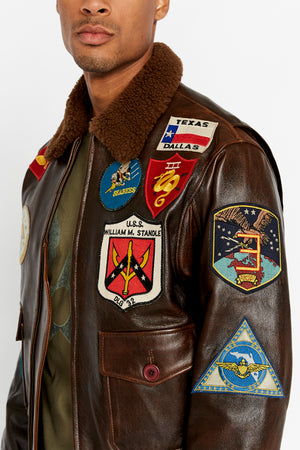 Detailed view of Top Gun colorful patches on left side of bodice.  Six patches applied on chest and left arm including Avirex patch. Flap pocket with button closure does not contain a patch