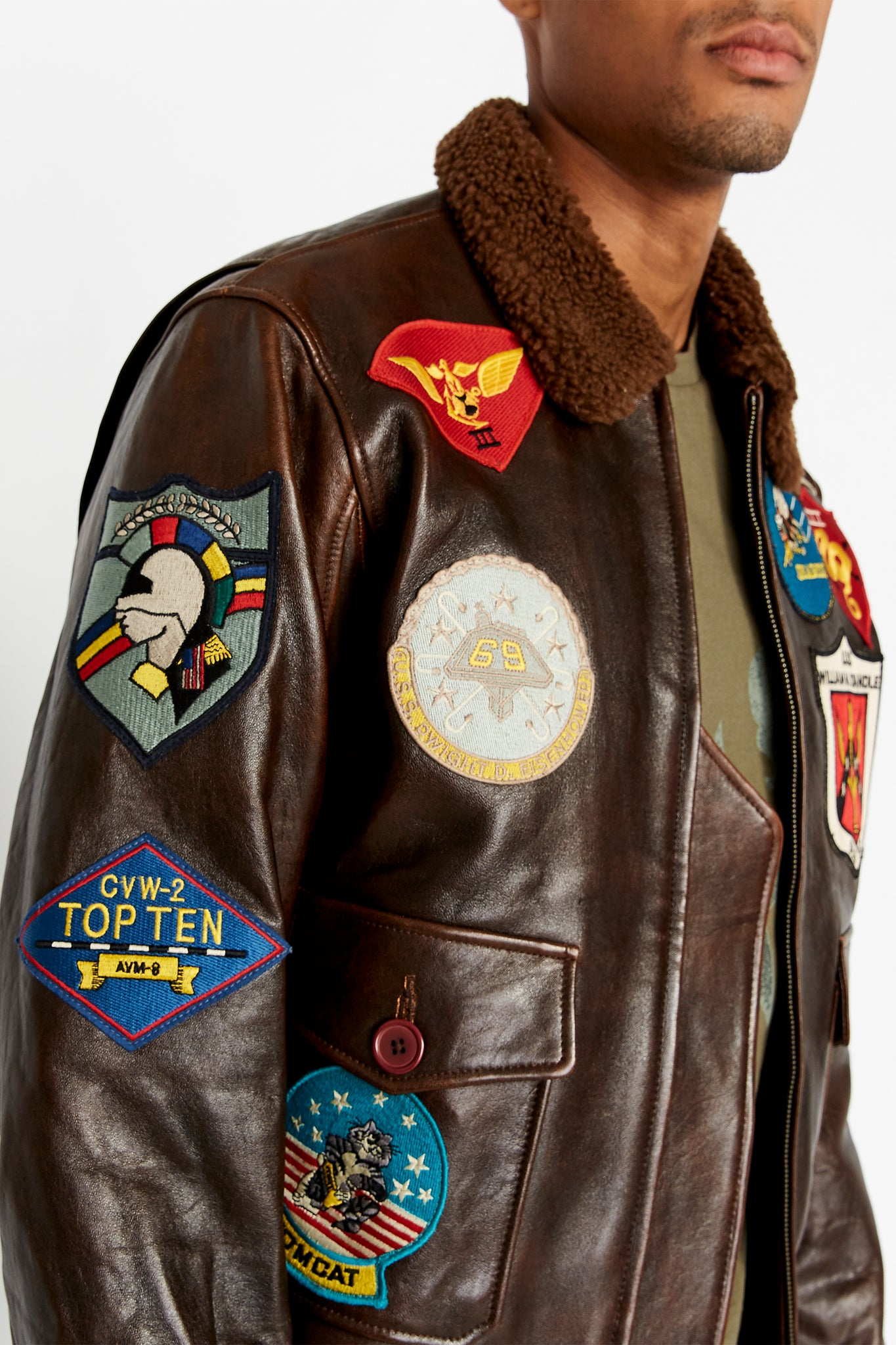 Detailed view of Top Gun colorful patches on right side of bodice.  Five patches applied, including Tom Cat patch on right flap pocket with button closure