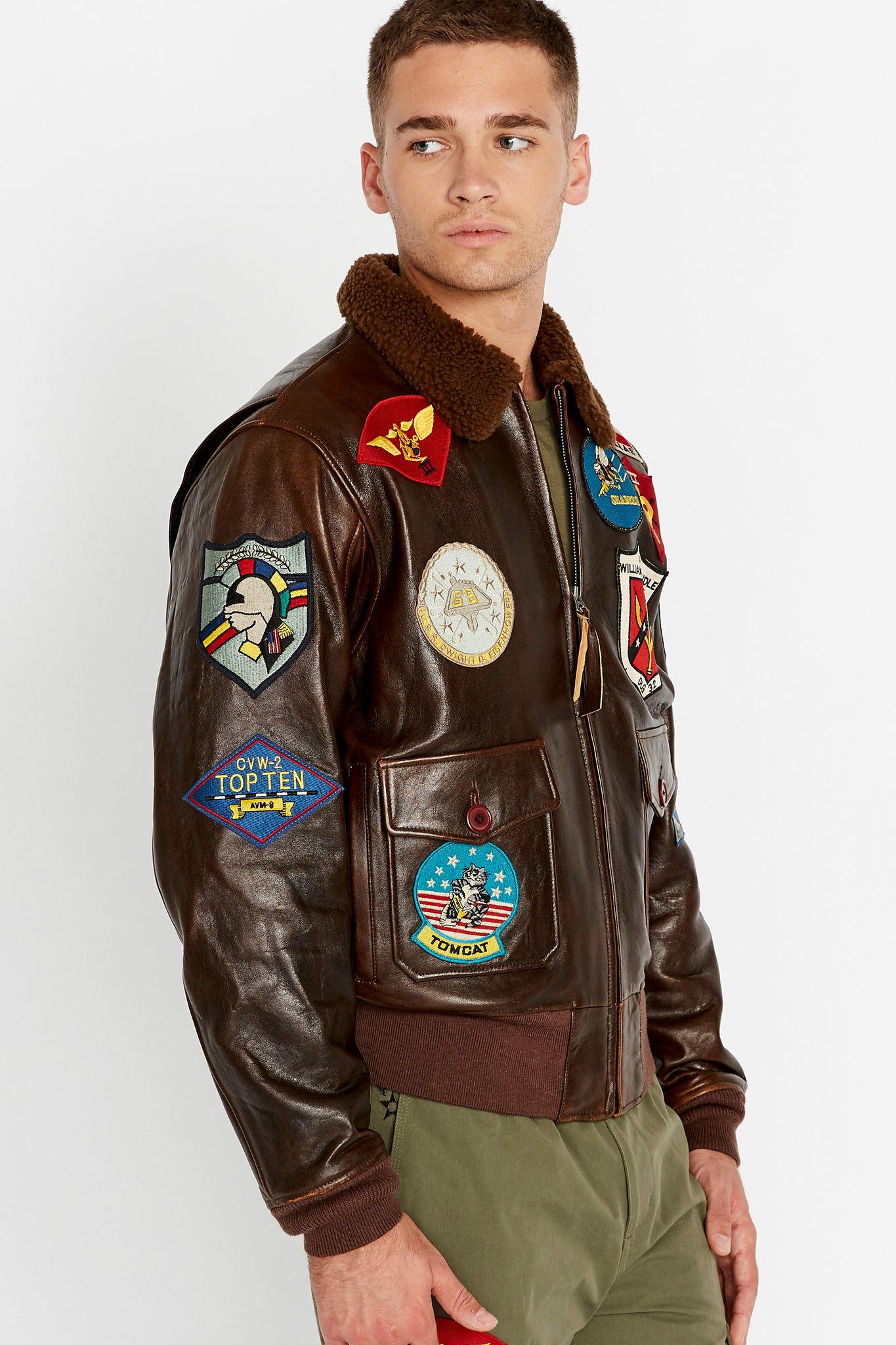 Side view of men wearing a brown Top Gun G-1 leather jacket with shearling fur lined collar and colorful authentic Top gun patches design on bodice