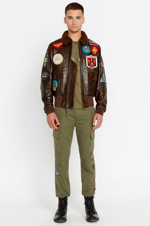 Full view of men wearing a brwon open Top Gun G-1 leather jacket with shearling fur lined collar and colorful Top gun patches design on bodice and olive pants