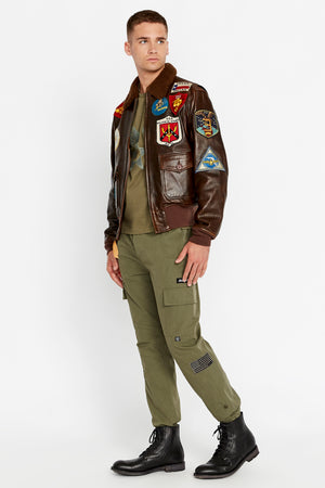 Side full view of men wearing a brown open Top Gun G-1 leather jacket with shearling fur lined collar and colorful Top gun patch design on bodice and olive pants