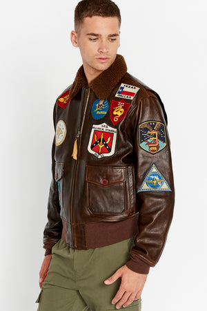 Side view of men wearing a brown fully zipped Top Gun G-1 leather jacket with shearling fur lined collar and colorful authentic Top gun patches design on bodice.