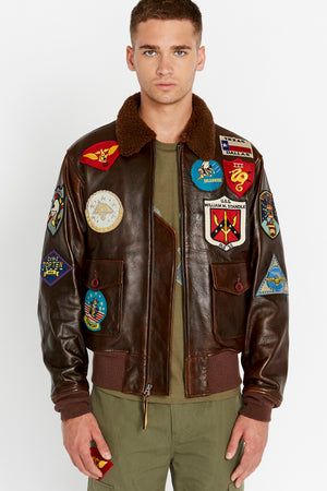 Front view of men wearing a brown open Top Gun G-1 leather jacket with shearling fur lined collar and colorful Top gun patches design on bodice