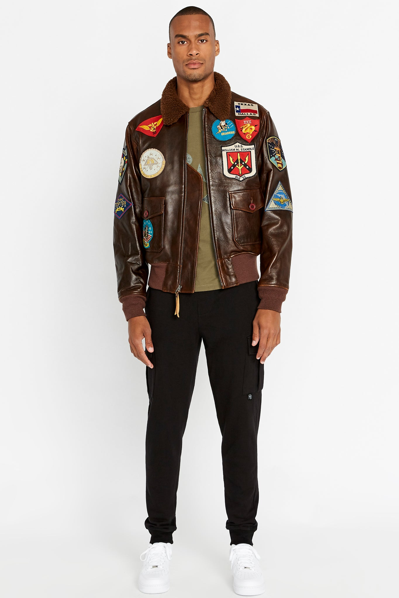 Full view of men wearing a brwon open Top Gun G-1 leather jacket with shearling fur lined collar and colorful Top gun patches design on bodice and black pants