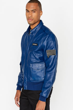 Side view of men wearing a fully zipped blue leather bomber jacket with snap down collar and two flap snap prockets, Avirex logo patch on the chest and one patch on the left sleeve