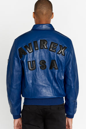 Back view of men wearing blue leather bomber jacket with bold text lettering Avirex USA