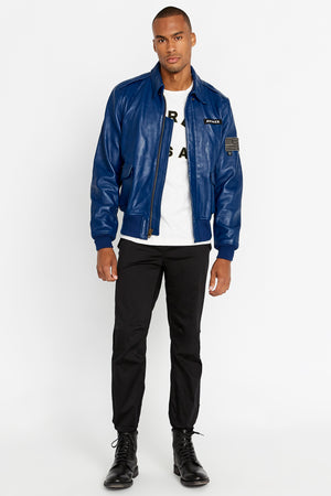 Full front view of men wearing an open blue leather bomber jacket with snap down collar and two flap snap prockets, Avirex logo patch on the chest and one patch on the left sleeve and black pants