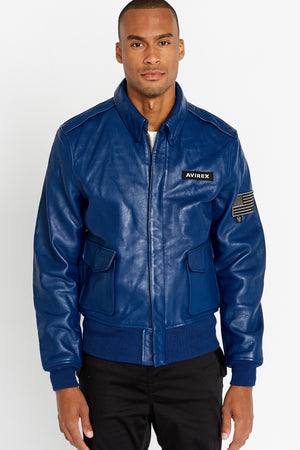 Front view of men wearing a fully zipped blue leather bomber jacket with snap down collar and two flap snap prockets, Avirex logo patch on the chest and one patch on the left sleeve
