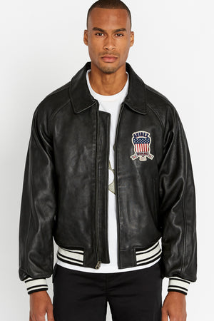 Front view of men wearing an open black original aviation bomber leather jacket with patch on the chest and stripes on knit ribs