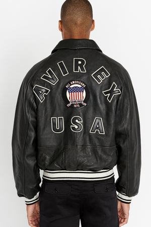 Back view of men wearing black original aviation bomber leather jacket with bold back text and stripes on knit ribs