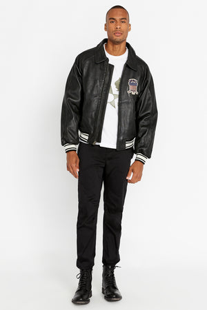 Front view of men wearing an open black original aviation bomber leather jacket with patch on the chest and stripes on knit ribs and black pants