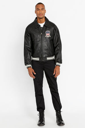 Front view of men wearing a fully zipped black original aviation bomber leather jacket with patch on the chest and stripes on knit ribs and black pants