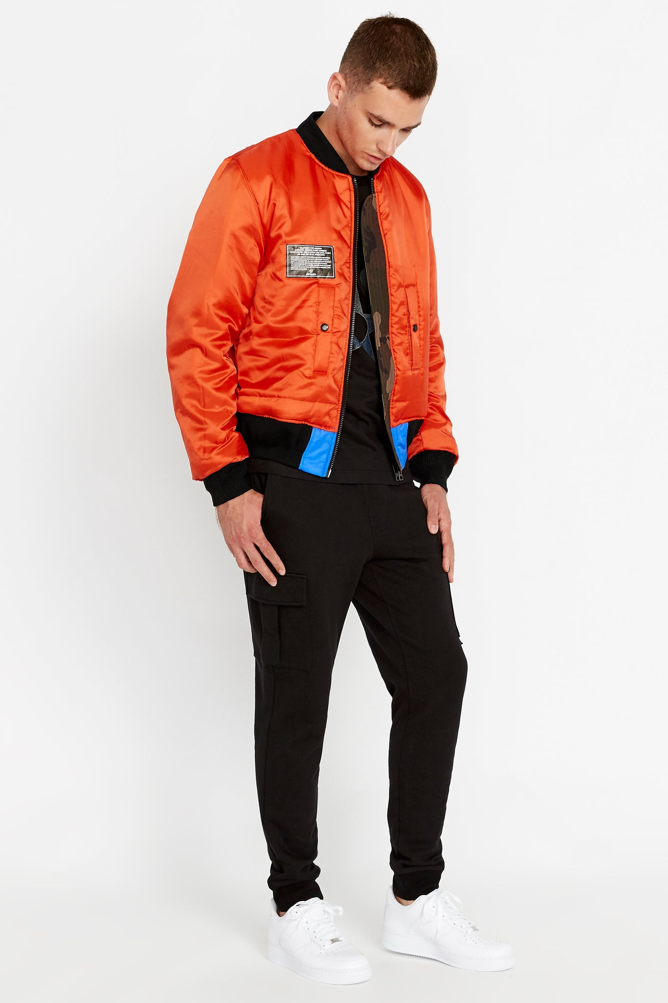 Full side view of men wearing an open reversed orange bomber jacket with one patch on the right chest and two pockets and black pants