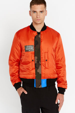 Front view of men wearing a fully zipped reversed orange bomber jacket with one patch on the right chest and two pockets