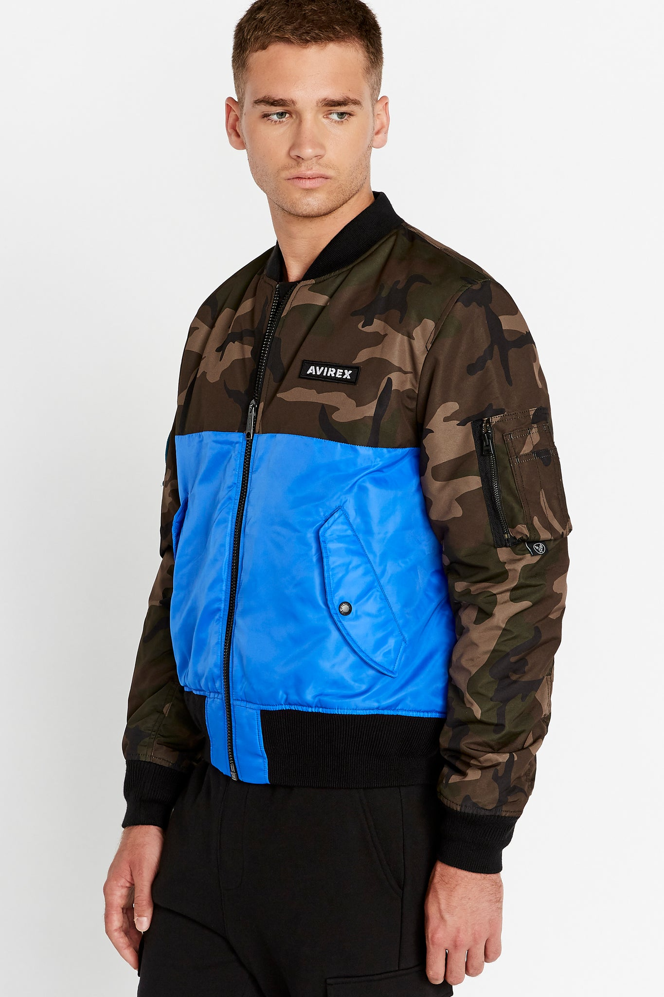 Side view of men wearing a fully zipped royal blue bomber jacket with camo print on the chest and sleeve, Avirex logo patch on the left chest and two side flap pockets and one utility pocket on left sleeve