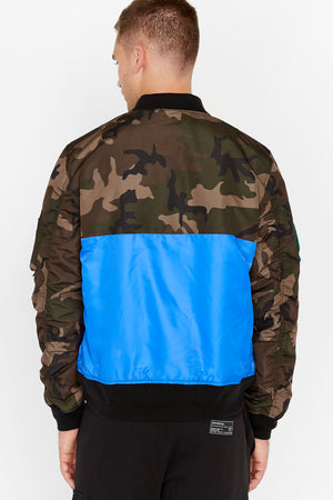 Back view of men wearing a royal blue bomber jacket with camo print on the chest and sleeve