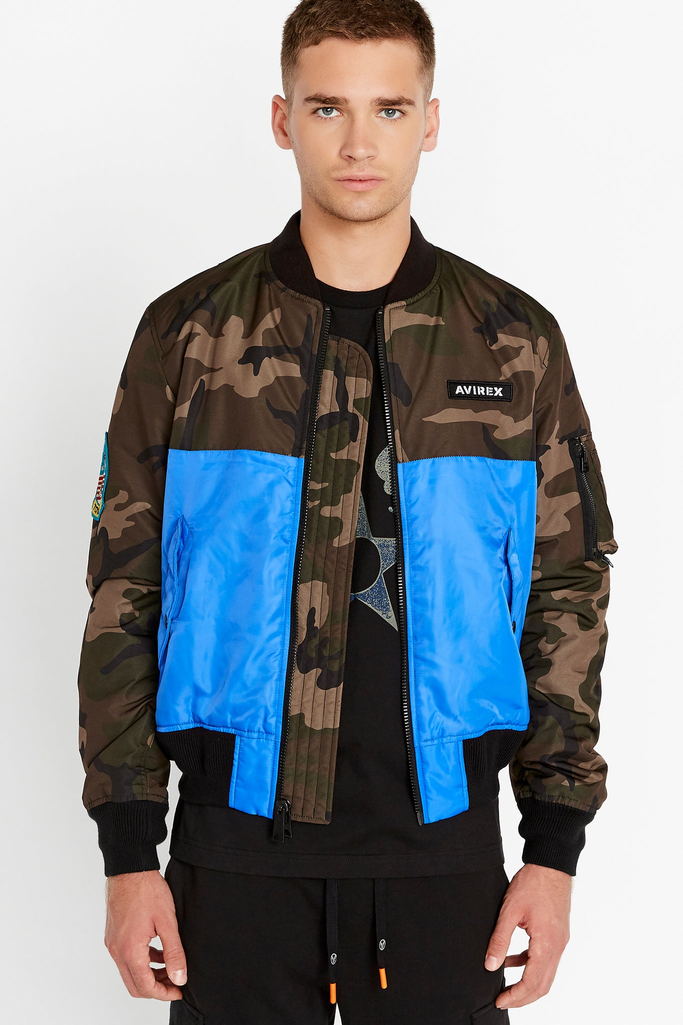 Front view of men wearing an open royal blue bomber jacket with camo print on the chest and sleeve, Avirex logo patch on the left chest and two side flap pockets and one utility pocket on left sleeve