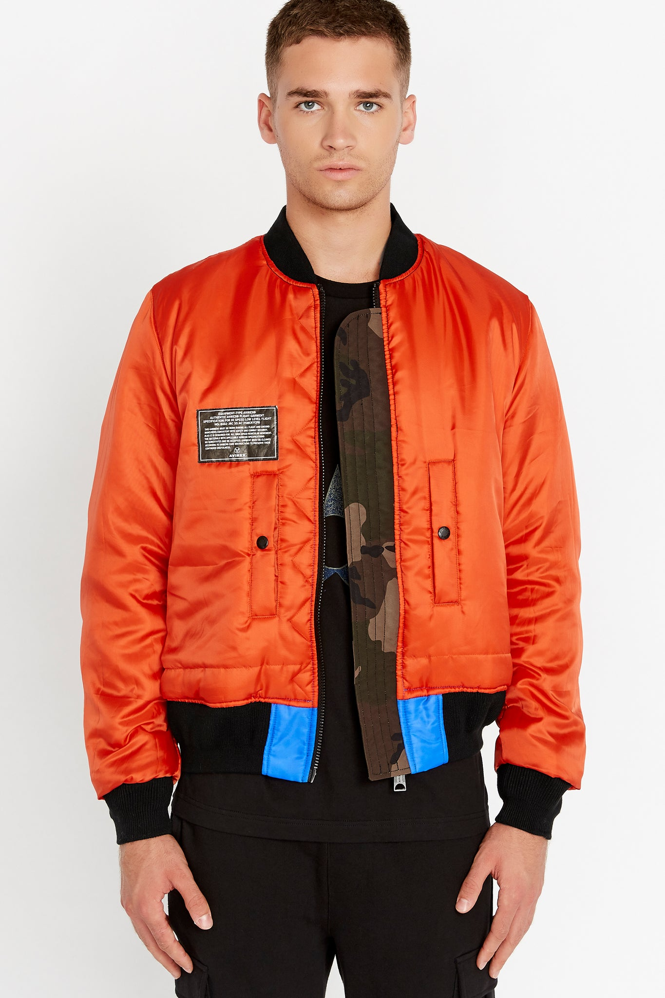 Front view of men wearing an open reversed orange bomber jacket with one patch on the right chest and two pockets