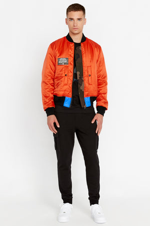 Full front view of men wearing an open reversed orange bomber jacket with one patch on the right chest and two pockets and black pants