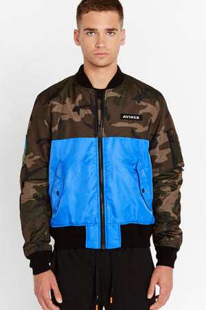 Front view of men wearing a fully zipped royal blue bomber jacket with camo print on the chest and sleeve, Avirex logo patch on the left chest and two side flap pockets and one utility pocket on left sleeve