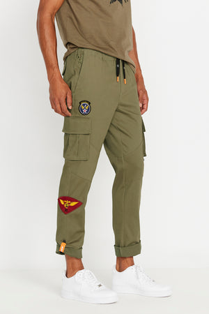Side view of multi patches design olive pants with side cargo pockets and rolled up hem with reflective logo, branded draw cords