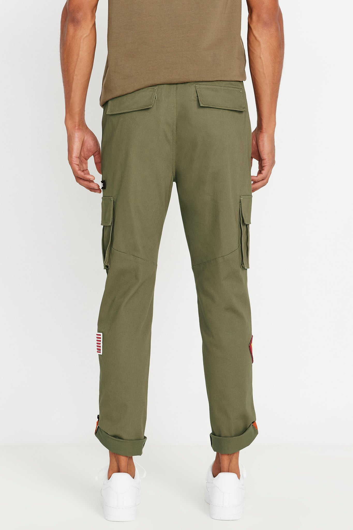 Back view of olive pants with two flap cover pockets and rolled up hem with reflective logo
