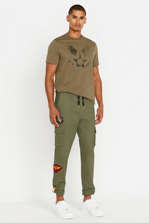 Full view of man wearing a multi patches design olive pants with side cargo pockets and rolled up hem with reflective logo and olive short sleeve crew neck T-shirt