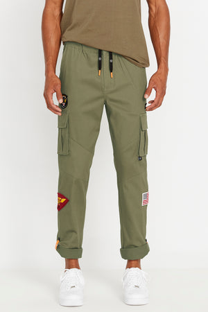 Front view of multi patches design olive pants with side cargo pockets and rolled up hem with reflective logo