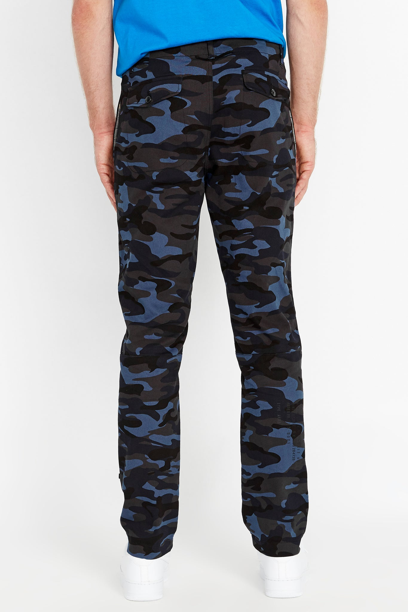 Back view of navy camo print pants with two button flap pockets on the back and text print on right hem