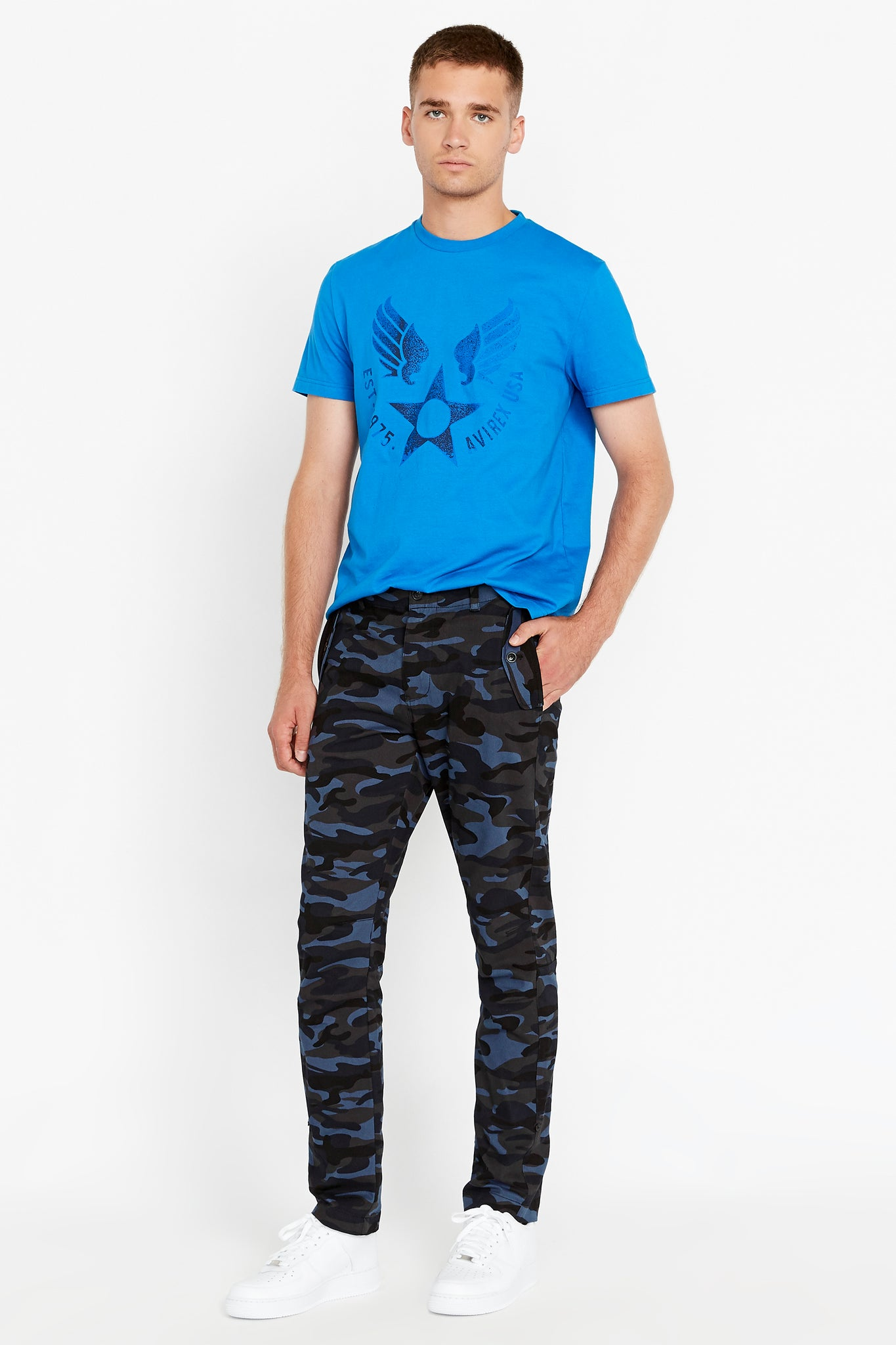Full view of men wearing navy camo print pants with two pockets on the side and blue short sleeve crew neck T-shirt