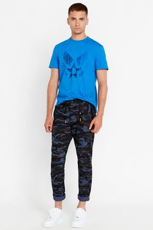 Full view of men wearing navy camo print pants with branded draw cords and two pockets on the side and bottom hem rolled with reflective logo and blue short sleeve crew neck T-shirt