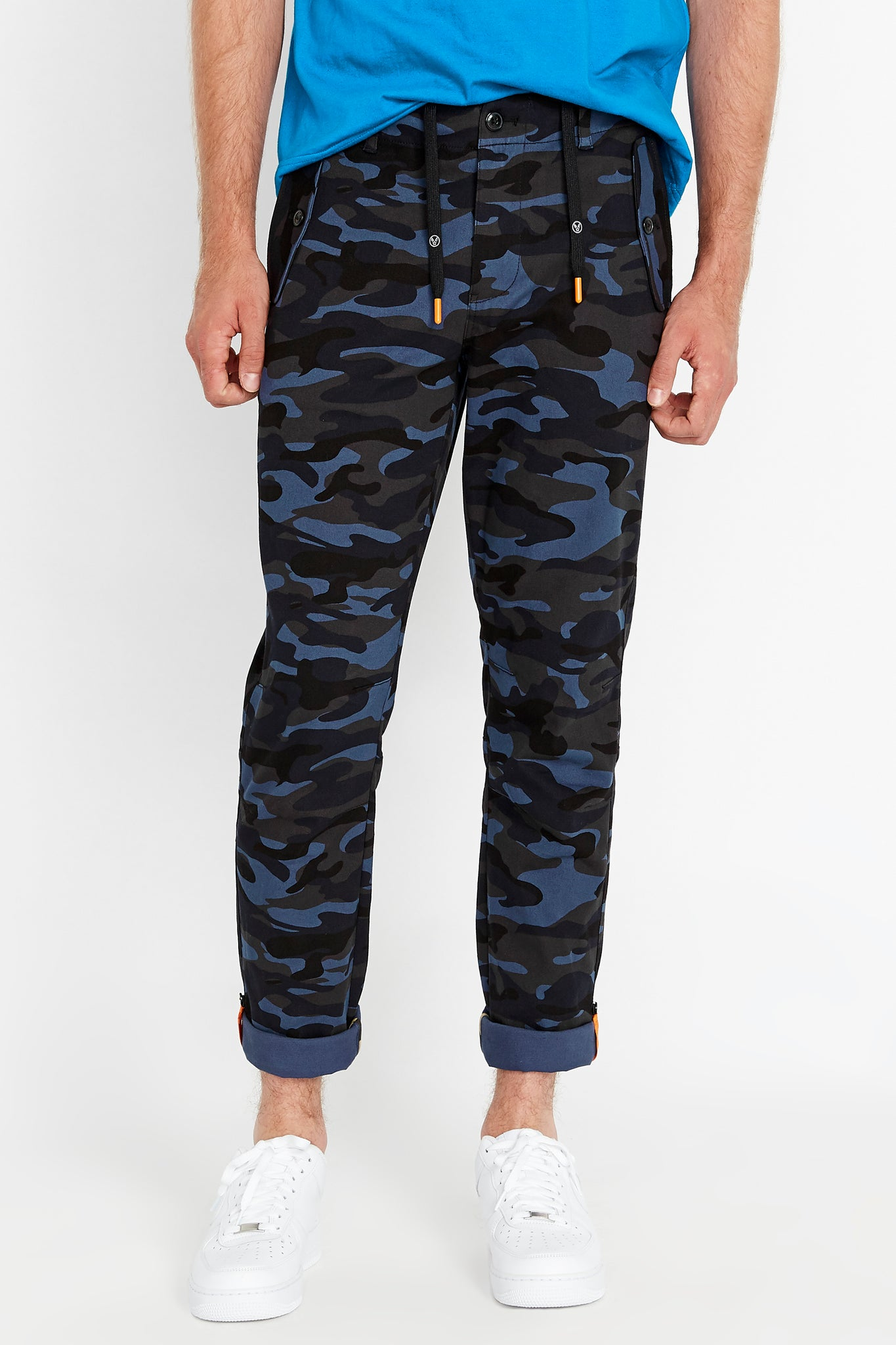 Front view of navy camo print pants with branded draw cords and two pockets on the side and bottom hem rolled with reflective logo