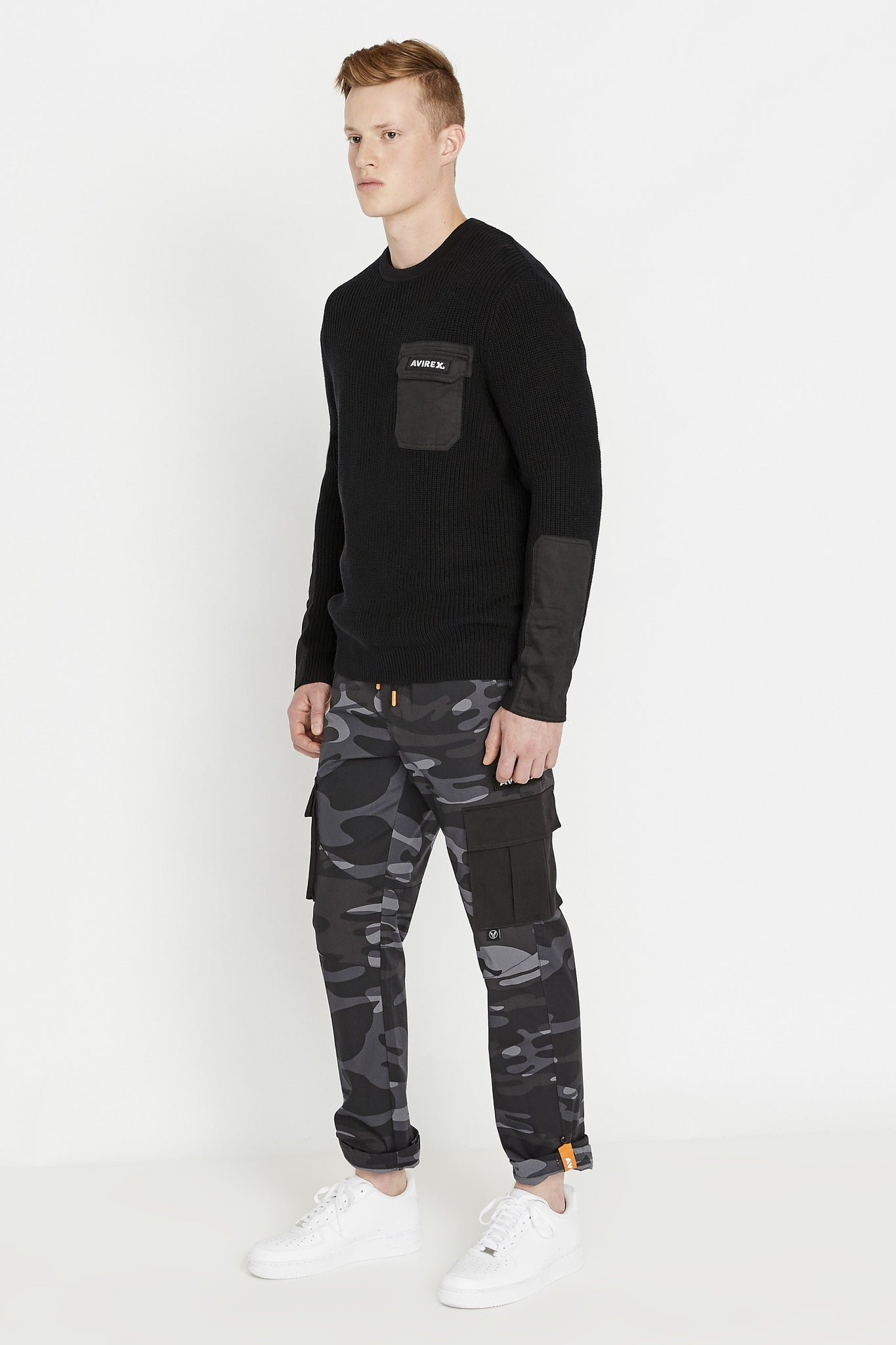Side full view of men wearing a black long sleeve crew neck sweater with pocket and patch on the chest and patches on sleeves and grey camo print pants