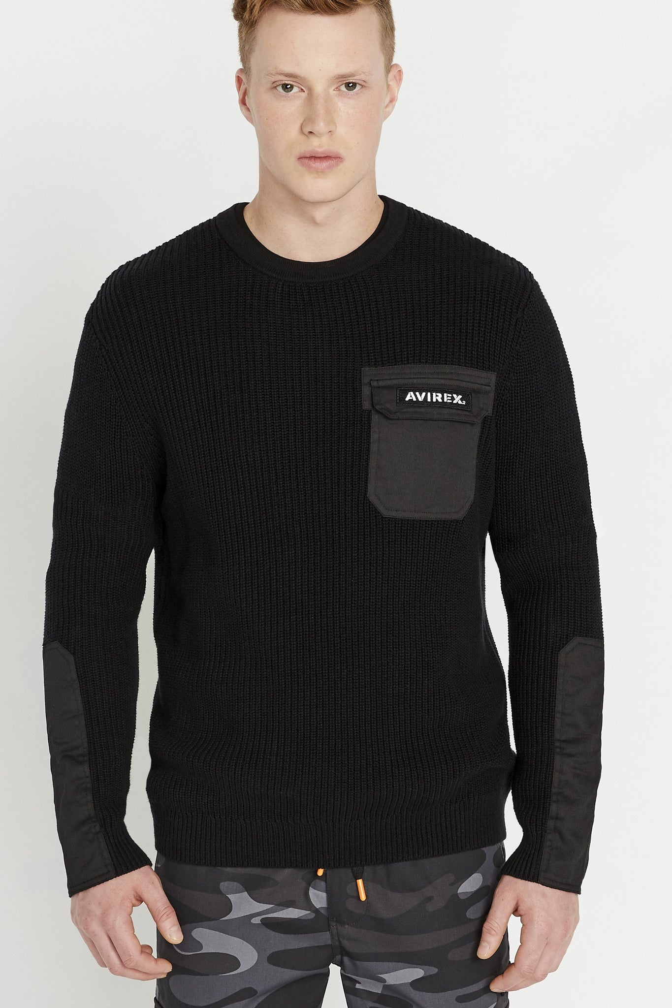 Men wearing a black long sleeve crew neck sweater with pocket and patch on the chest and patches on sleeves