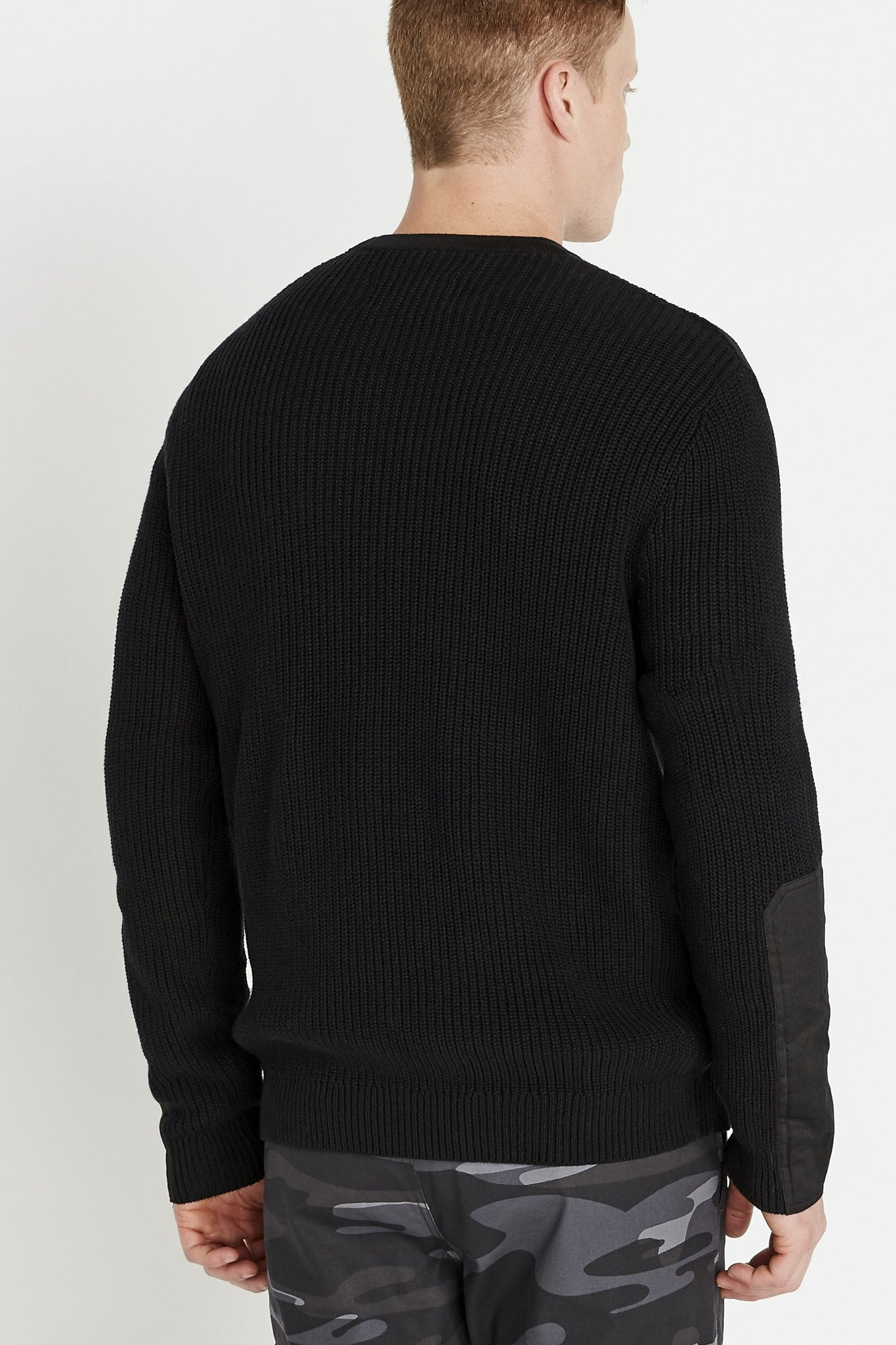 Back view of men wearing a black long sleeve crew neck sweater with patches on sleeves
