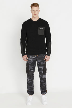 Full view of men wearing a black long sleeve crew neck sweater with pocket and patch on the chest and patches on sleeves and grey camo print pants