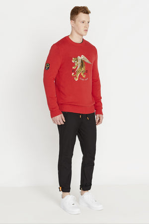 Side full view of men wearing a red long sleeve crew neck sweater with front flying tiger embroidery and a patch on the right sleeve and black pants