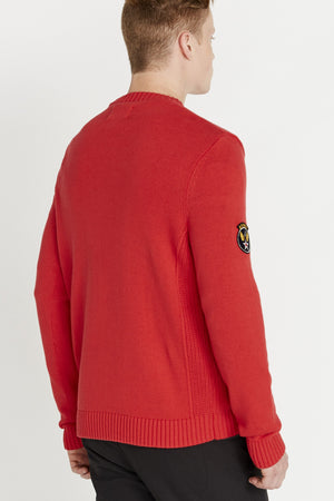 Back view of men wearing a red long sleeve crew neck sweater with a patch on the right sleeve