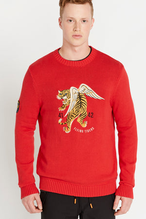 Men wearing a red long sleeve crew neck sweater with front flying tiger embroidery and a patch on the right sleeve
