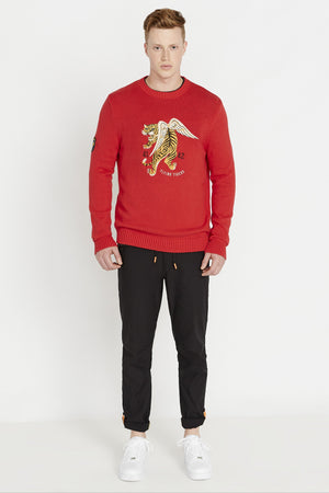 Full view of men wearing a red long sleeve crew neck sweater with front flying tiger embroidery and a patch on the right sleeve and black pants