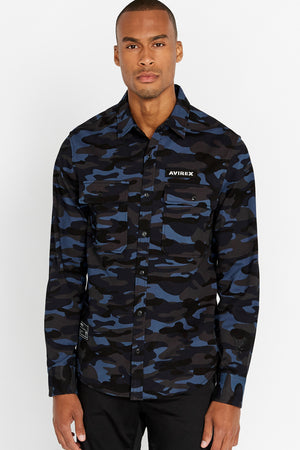 Men wearing a blue camo print long sleeve shirt with two front button-flap pockets white logo on left chest and white patch on right bottom corner