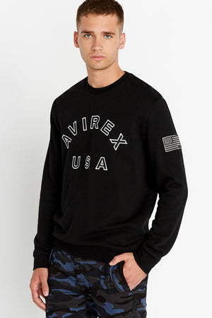 Side view of men wearing a black long sleeve crew neck sweater with bold front text and a patch on the left sleeve