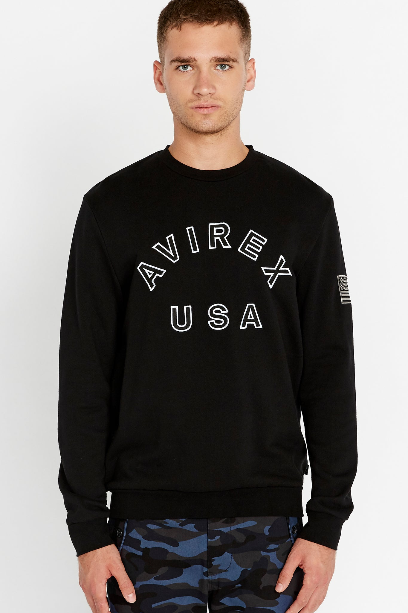 Men wearing a black long sleeve crew neck sweater with bold front text and a patch on the left sleeve