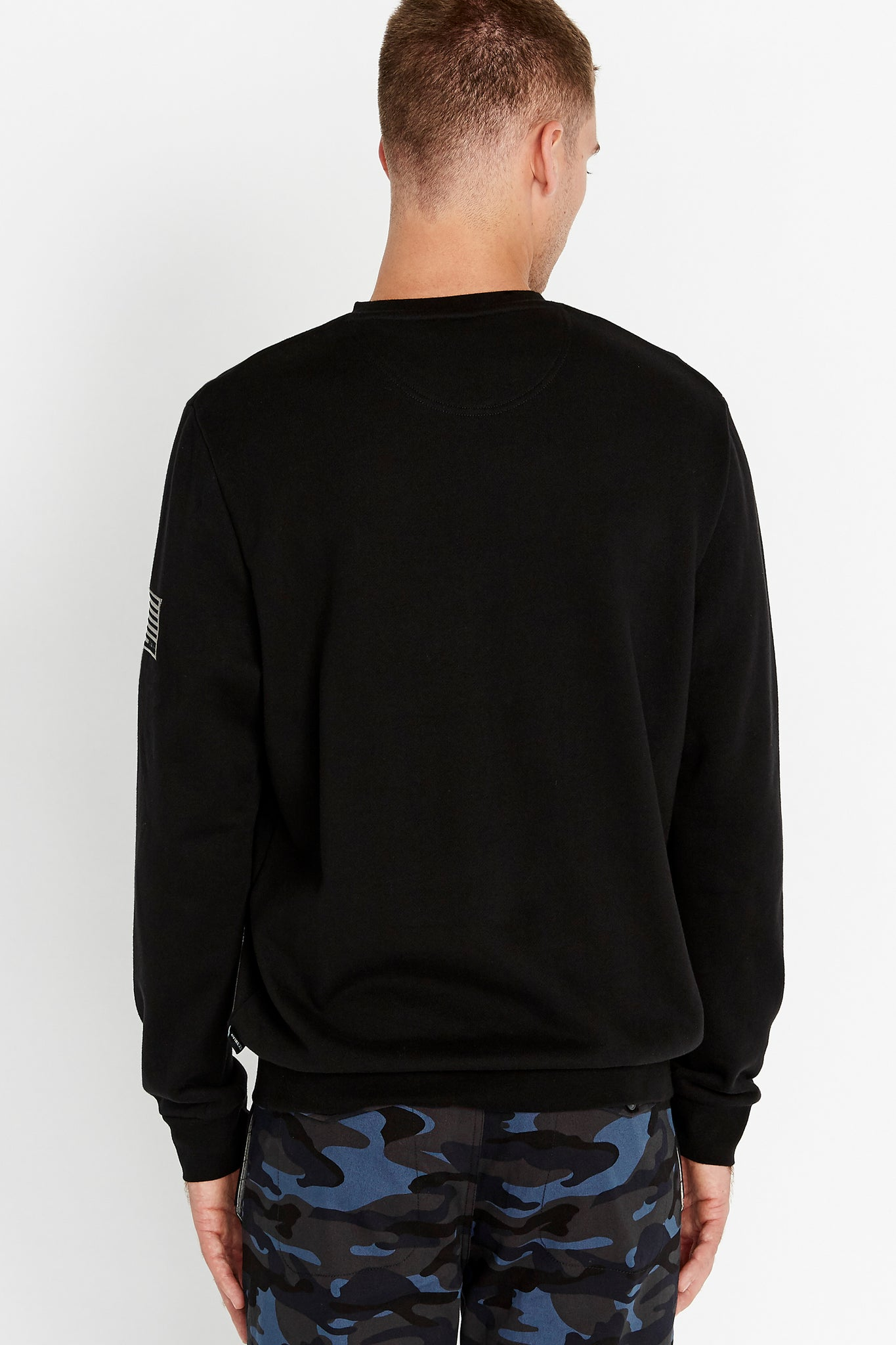 Back view of men wearing a black long sleeve crew neck sweater