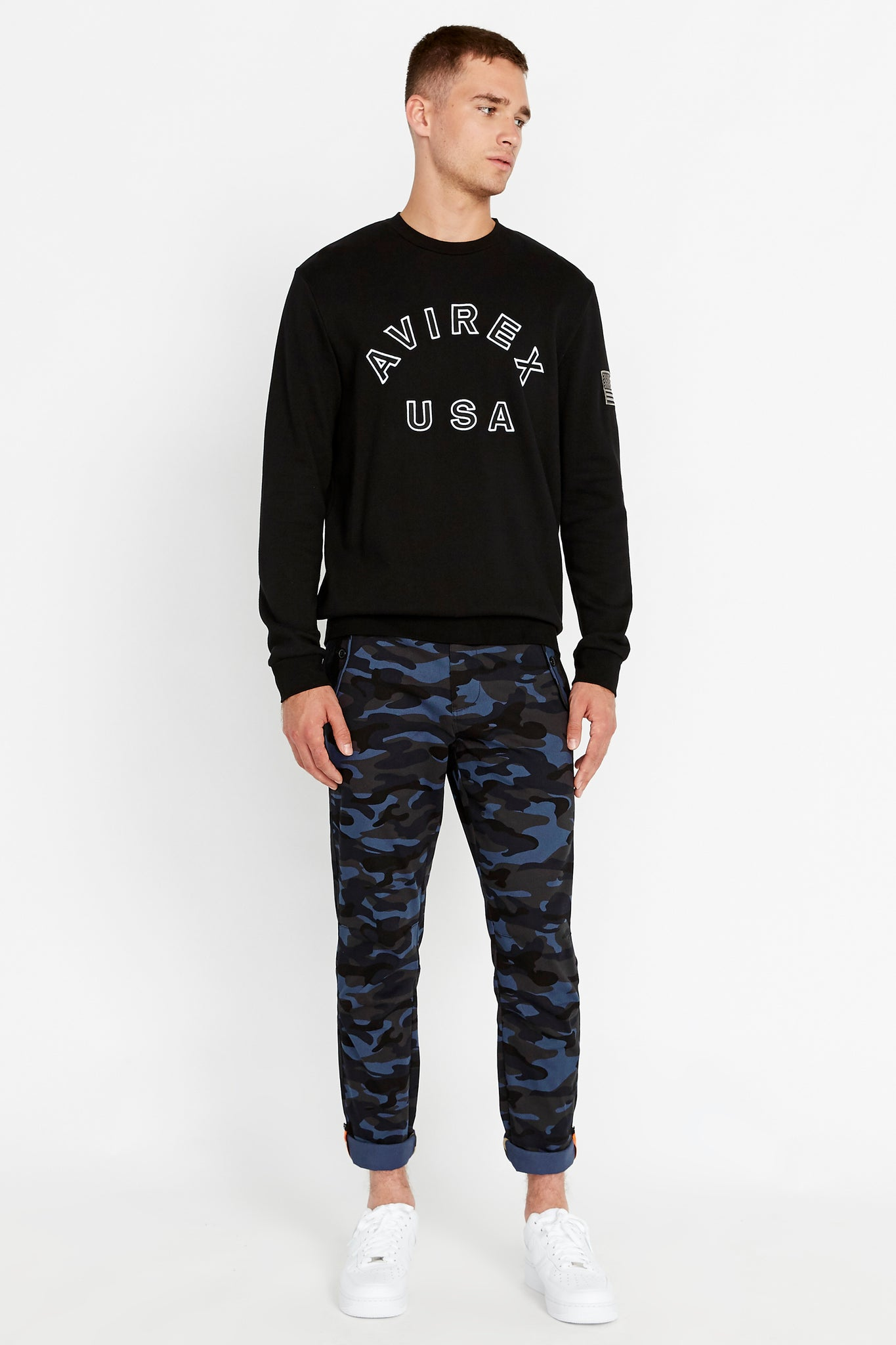 Full view of men wearing a black long sleeve crew neck sweater with bold front text and a patch on the left sleeve and blue camo print pants