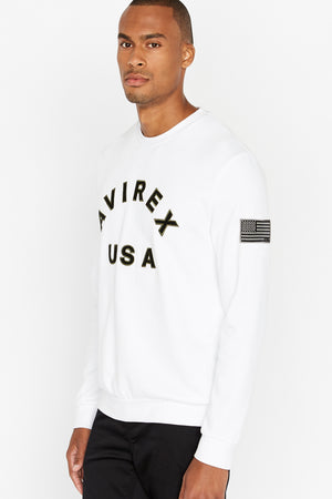 Side view of men wearing a white long sleeve crew neck sweater with bold front text and a patch on the left sleeve