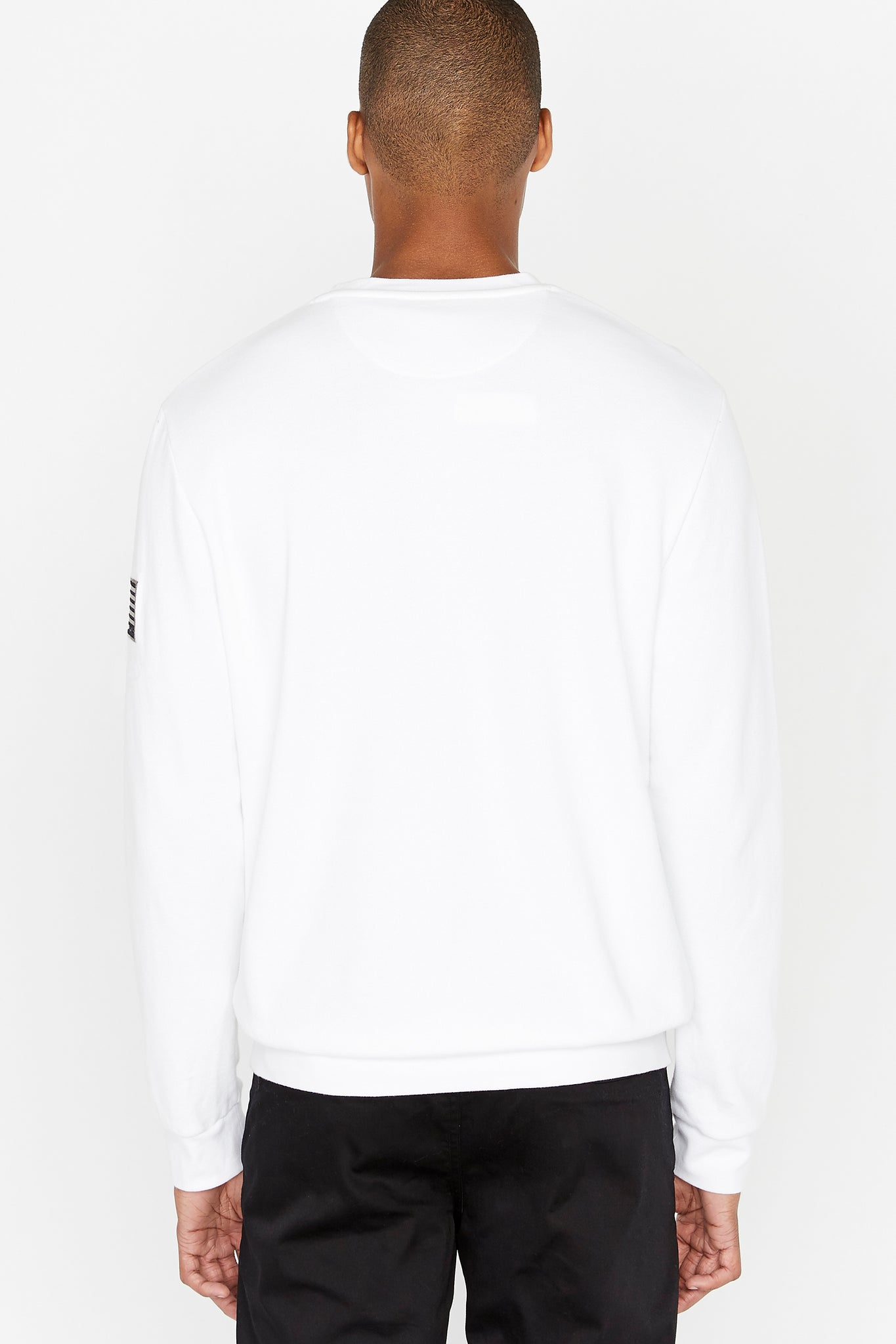 Back view of men wearing a white long sleeve crew neck sweater