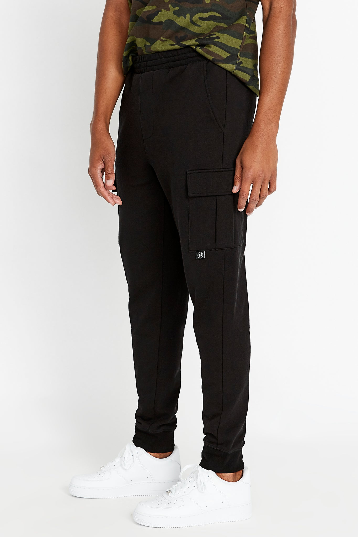 Side view of men's drawstring pant with cargo pockets.  Elastic band closing at hem. Avirex logo on pocket