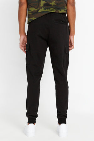 Back view of Men's drawstring pant with cargo pockets.  Back pocket. Elastic band closing at hem